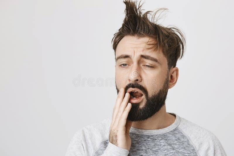Gähnender und schläfriger bärtiger Kerl mit unordentlicher Haarbedeckung mouth mit der Hand und steht über grauem Hintergrund Man stockbilder