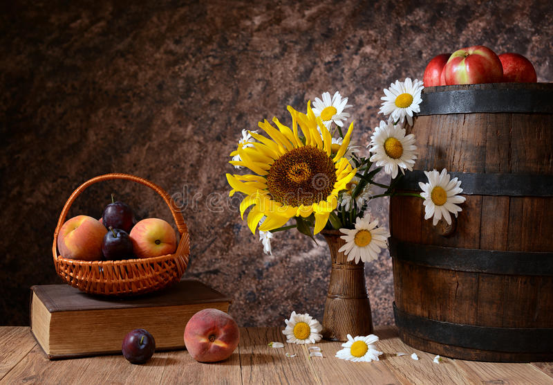 Gänseblümchen blüht in einem Vase mit frischen Früchten in einem vicker Korb stockfotografie
