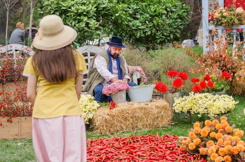 Gärtner, der Blumenblumenstrauß im bunten Garten während des jährlichen Festivals macht lizenzfreie stockfotografie