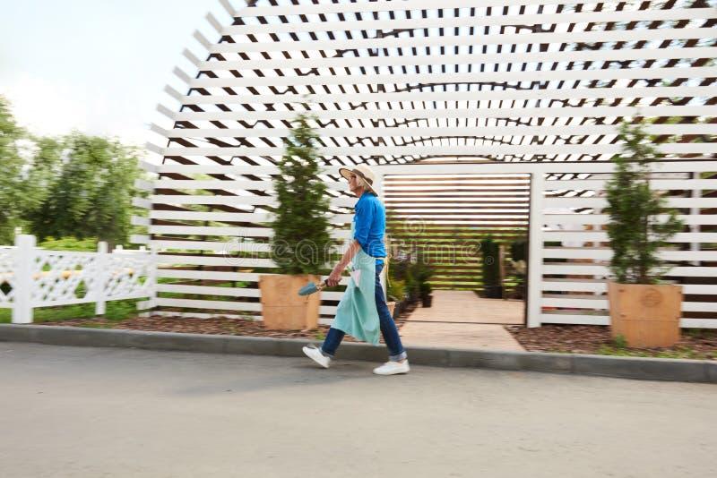 Gärtner Walking Past Greenhouse lizenzfreies stockbild