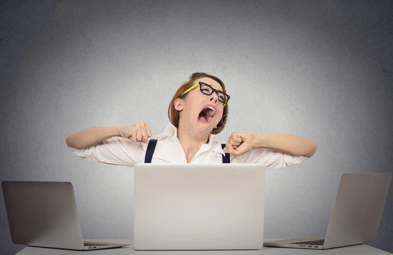 Gäspa sammanträde för affärskvinna på skrivbordet med datorer royaltyfri fotografi