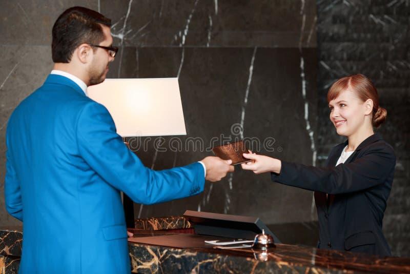 Gäst som meddelar med en receptionist arkivbilder