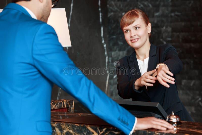 Gäst som meddelar med en receptionist arkivfoto