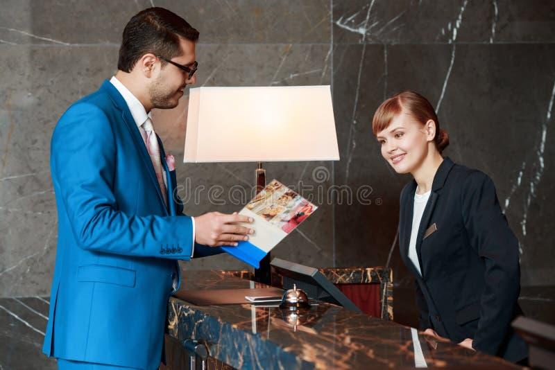 Gäst som meddelar med en receptionist royaltyfri fotografi