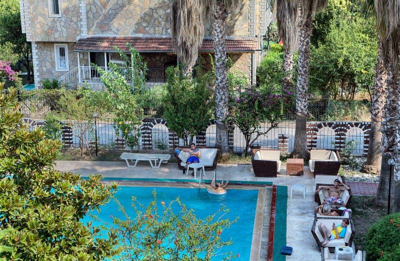 Gäste des kleinen Hotels, entspannen sich durch den Swimmingpool im Freien lizenzfreies stockbild