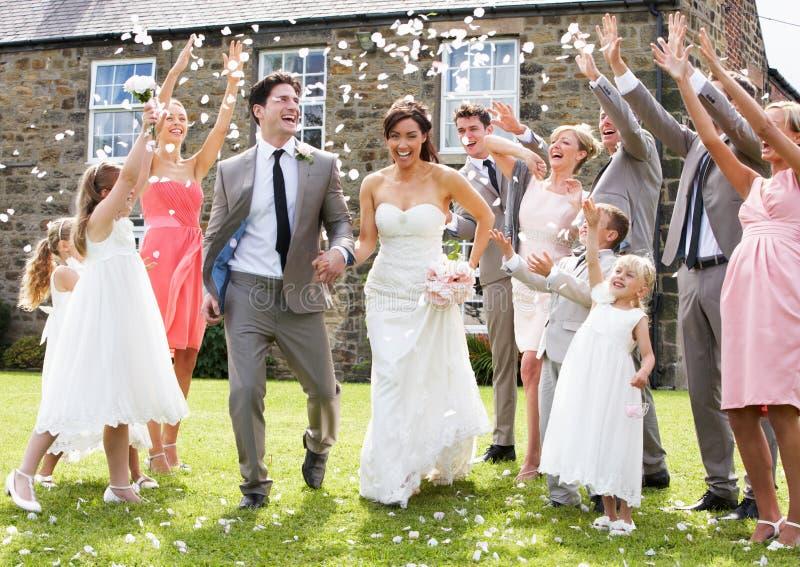 Gäste, die Konfettis über Braut und Bräutigam werfen stockfotos