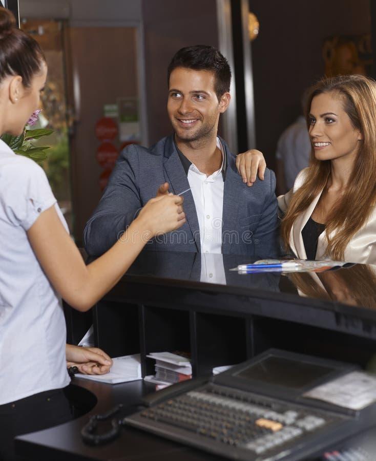 Gäste, die Schlüsselkarte an der Hotelaufnahme empfangen lizenzfreie stockfotos