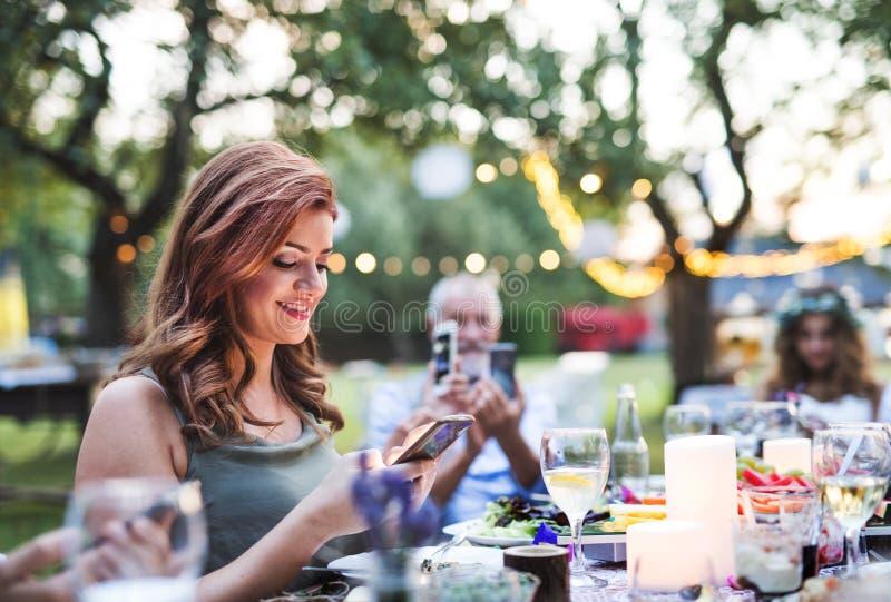 Gäste mit den Smartphones, die draußen Foto am Hochzeitsempfang machen stockfotografie