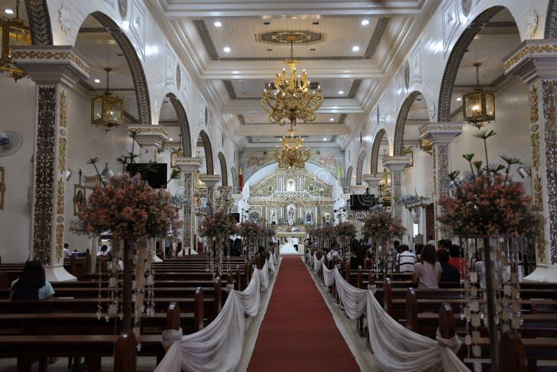 Gäster som deltar i en bröllopsceremoni i Barasoain-kyrkan, Bulacan, Filippinerna, 17 augusti 2019 arkivfoton