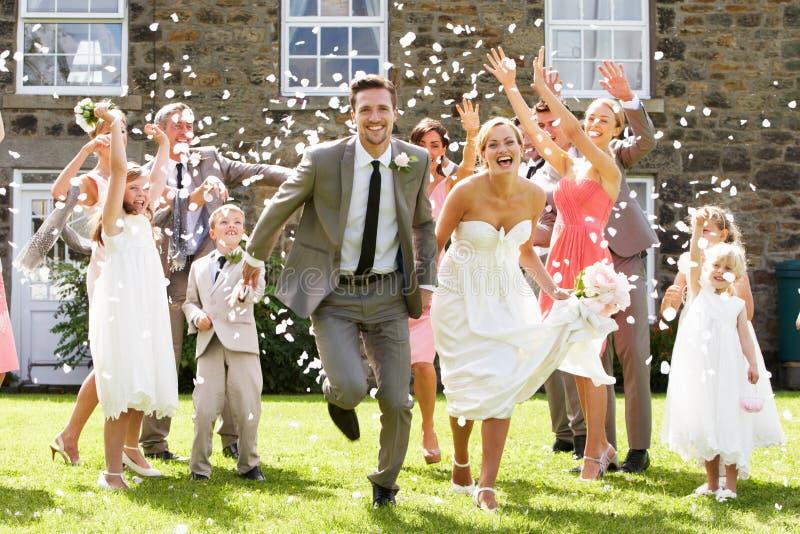 Gäster som kastar konfettier över brud och brudgum arkivbild