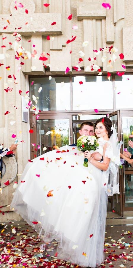 Gäster som kastar konfettier över bruden och brudgummen At Wedding royaltyfria bilder