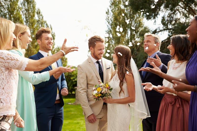 Gäster som kastar konfettier över bruden och brudgummen At Wedding royaltyfria foton