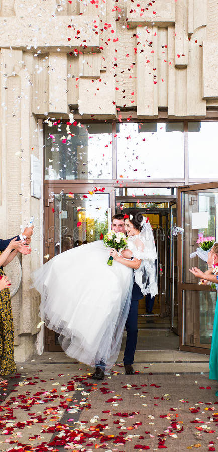 Gäster som kastar konfettier över bruden och brudgummen At Wedding royaltyfri foto