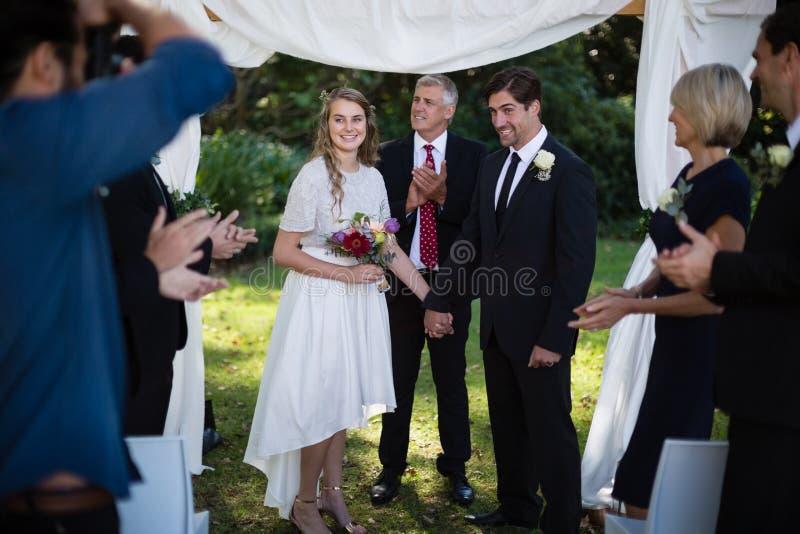 Gäster som nyligen applåderar för gift par royaltyfri bild
