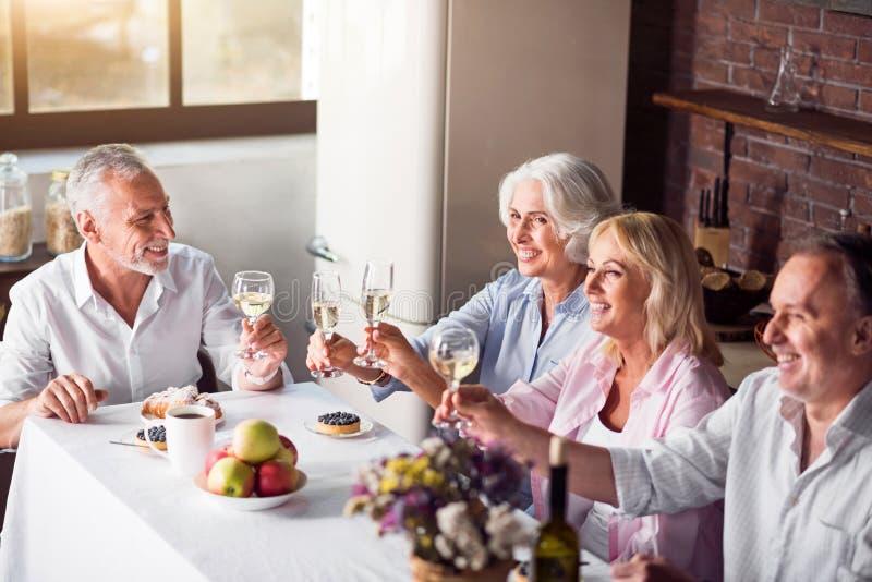 Gäster som sitter på köksbordet arkivfoto