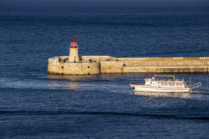 Głęboki błękitny seascape z Ricasoli falochronu latarnią morską i statkiem wycieczkowym przy Uroczystym schronieniem, Valletta, M zdjęcie stock