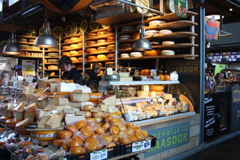 Gå att shoppa och köp smakliga ostar från rotterdam mejeriproducenter i den stora marknaden av metropolisen royaltyfria bilder