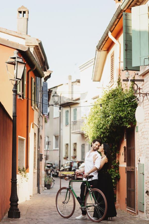 Gå ett par av vänner i gatorna av den gamla staden, med en cykel Kvinnan kramar försiktigt hennes man arkivfoto
