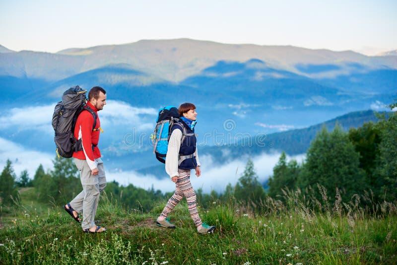 gå för berg Grabben och flickan med ryggsäckar är på banan på bergstoppet royaltyfria bilder