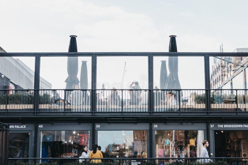 Gå för folk som är förgånget, och sitta på takkafét på BOXPARK Shoreditch, London, UK arkivfoton