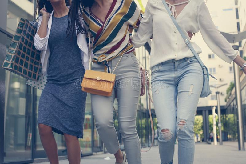 Gå för tre unga flickor som är lyckligt med shoppingpåsar arkivfoton