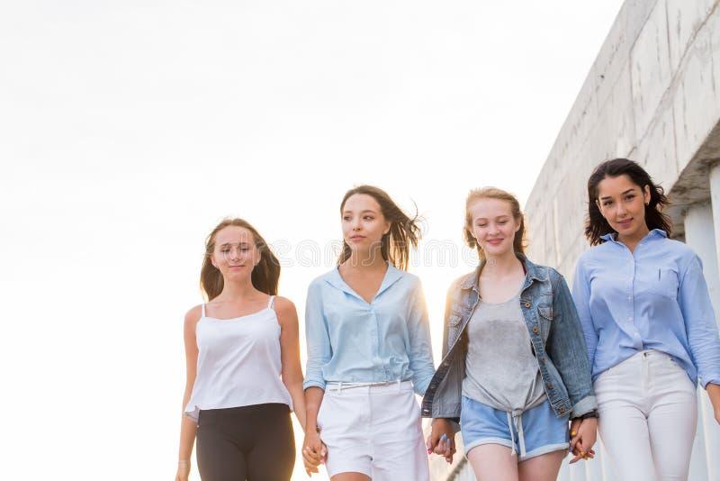 Gå fyra lyckliga vänner på gatan i bakgrunden av en vit himmel med kopieringsutrymme arkivfoton