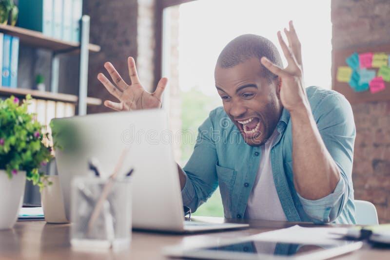 Gå galet på arbete Den unga mulattentreprenören är chockad av kuggningen som han har i affär, är han skrika och göra en gest som  arkivfoto