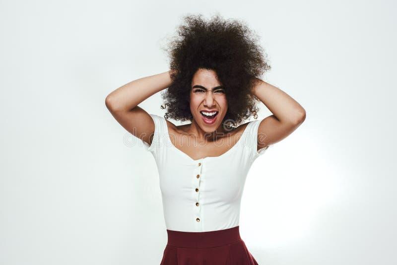 Gå galet! Skämtsam och upphetsad afro amerikansk kvinna som trycker på hennes lockiga hår, ser kameran och skriker stund arkivbilder