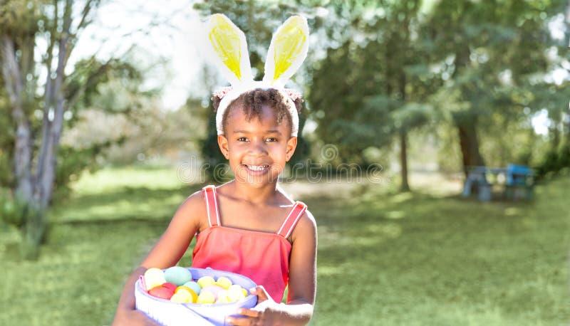 Gå i ax den bärande kaninen för den gulliga afrikansk amerikanflickan och att rymma påsklodisar royaltyfria bilder
