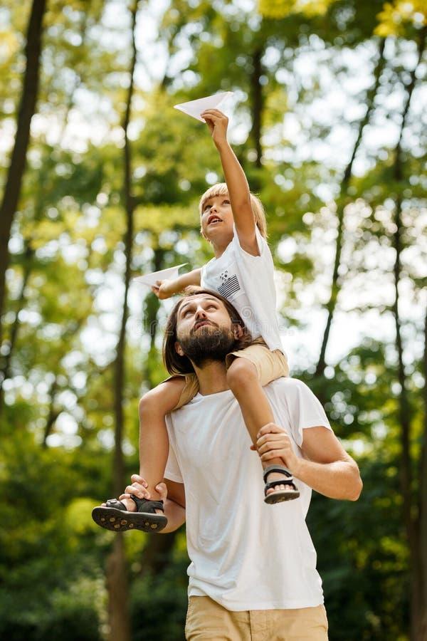 Gå i den iklädda blonda pojken för skog en vit t-skjorta som sitter på skuldrorna av hans skäggiga fader och uppehällen fotografering för bildbyråer
