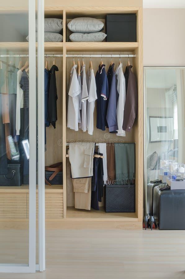 Gå i garderob med kläder som hänger i trägarderob arkivbilder
