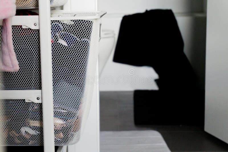 Gå i garderoben som leder till badrummet och att visa korgen av kläder och den svarta handduken som hänger över badkaret Visa arkivfoto