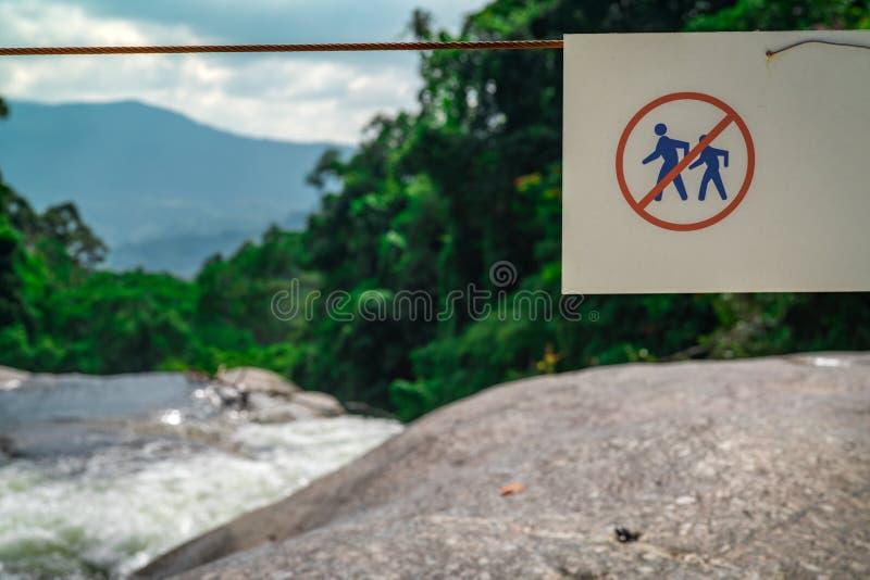Gå inte av slingan Varning undertecknar i nationalpark på vattenfallet i grön tropisk skog och berg mer mitt portföljtecken under arkivfoton