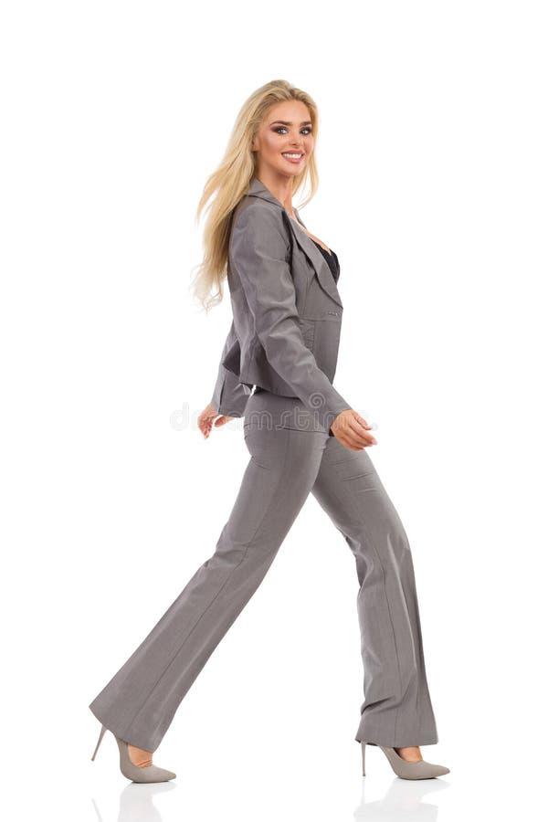Gå kvinnan i Gray Suit Is Smiling And som ser kameran royaltyfri fotografi