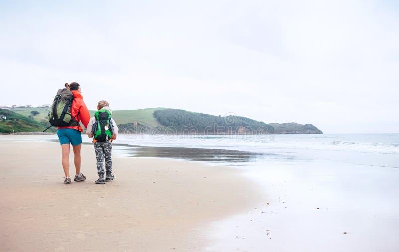 Gå lopp med barnet Modern och sonen går tillsammans på sand royaltyfri bild