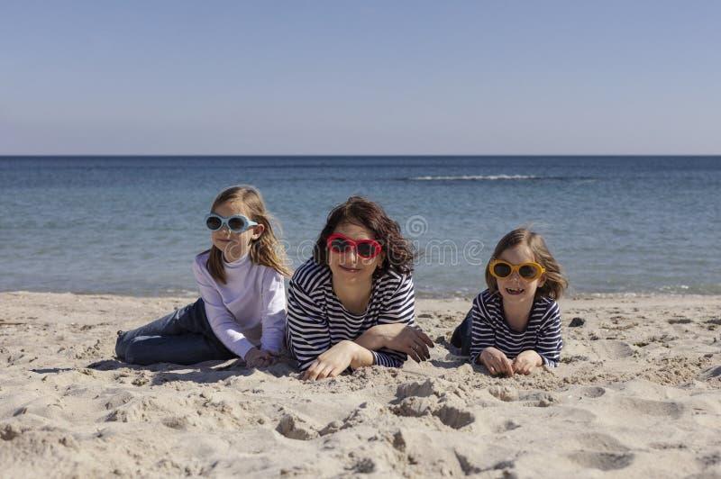 Gå mammor med barn på stranden Systrar 8 och 7 gamla år och yngre bror 3 gamla år spelar på havet royaltyfri bild
