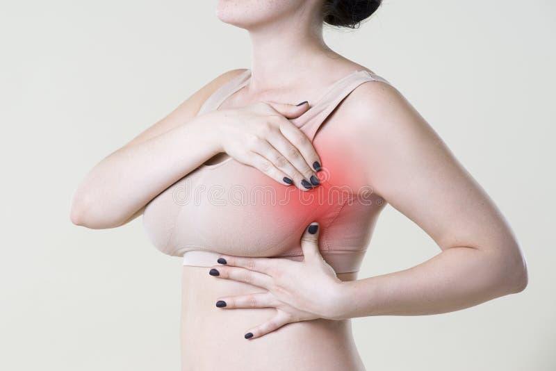 Gå mot provet, kvinnan som undersöker henne bröst för cancer, hjärtinfarkt, smärta i människokropp arkivbilder