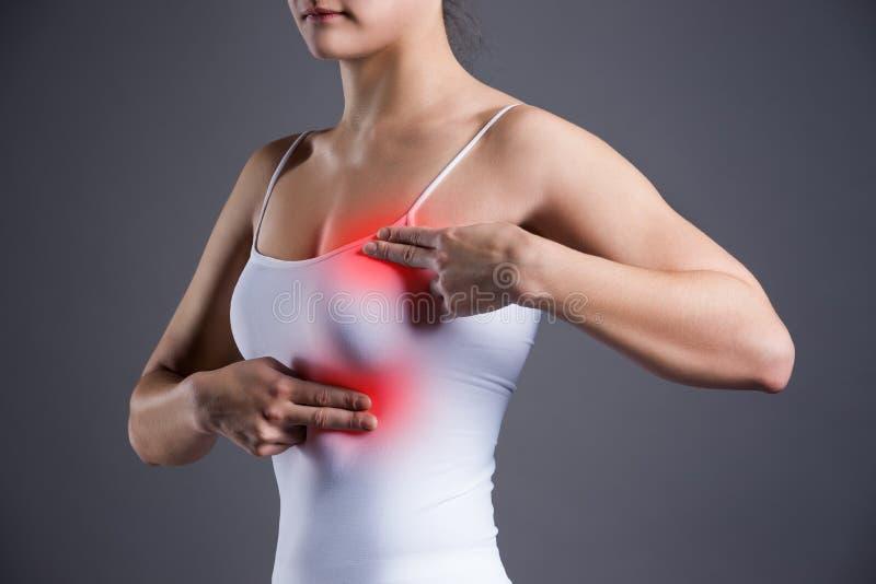 Gå mot provet, kvinnan som undersöker henne bröst för cancer, hjärtinfarkt, smärta i människokropp royaltyfri foto