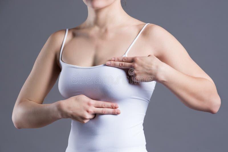 Gå mot provet, kvinnan som undersöker henne bröst för cancer, hjärtinfarkt, smärta i människokropp royaltyfri fotografi