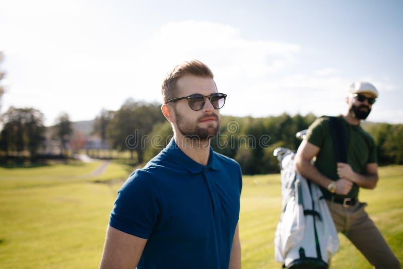 Gå och bärande påse för golfspelare på kurs under sommargam arkivfoto