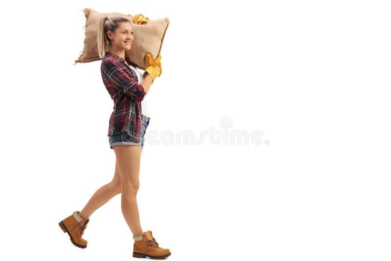 Gå och bärande säckvävsäck för kvinnlig bonde arkivfoto