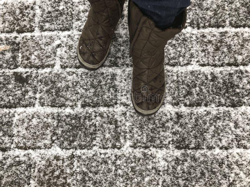 Gå på en kullerstengata under insnöad vinter arkivbild