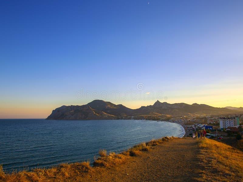Gå på kullarna under solnedgång över bergen och havet royaltyfria foton