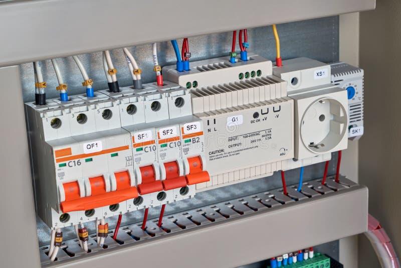 Gå runt säkerhetsbrytare, kontrollrelän, håligheten och termostaten i elektriskt kabinett fotografering för bildbyråer
