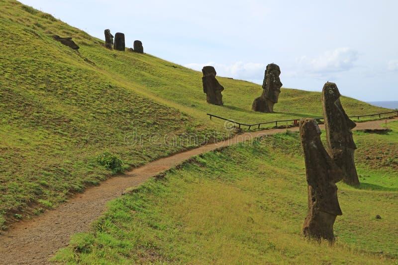 Gå rutten bland de legendariska jätteMoai statyerna på den Rano Raraku vulkan på påskön, Chile royaltyfri foto