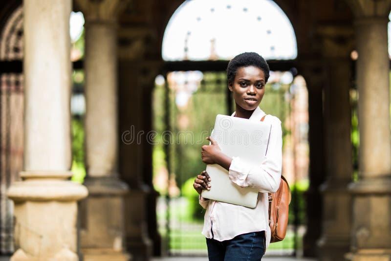 Gå till grupper Ung härlig afro amerikansk kvinnainnehavbärbar dator på universitetsområdebakgrund Universitet teknologi, affärsi royaltyfri bild