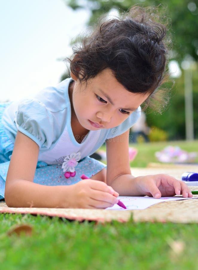 Gå tillbaka till skolan, flickateckningen och målning över grönt gräs arkivfoto