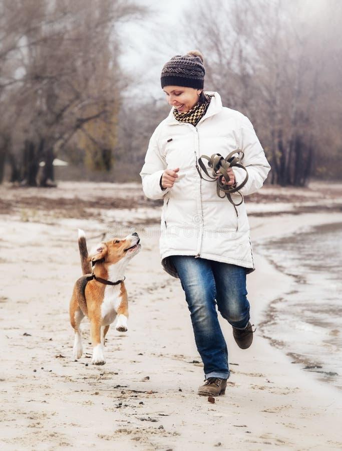 Gå tillsammans: flickan med beaglehunden kör längs den höstliga sandstranden royaltyfria foton