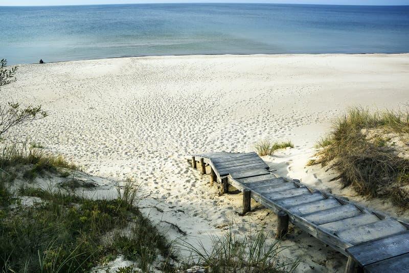 Gå ut på en trästege till havet med snövit sand royaltyfri foto