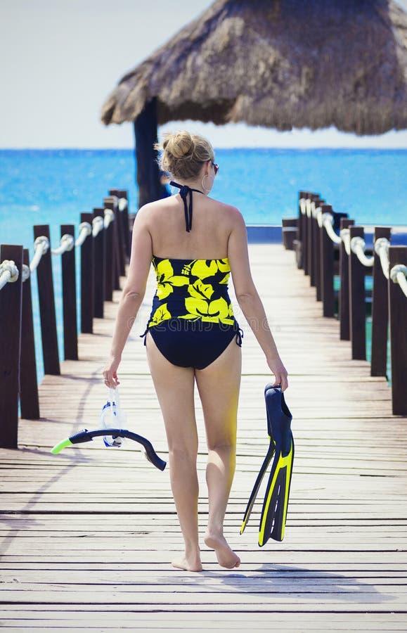 Gående snorkla för kvinna medan på en tropisk semester royaltyfri foto